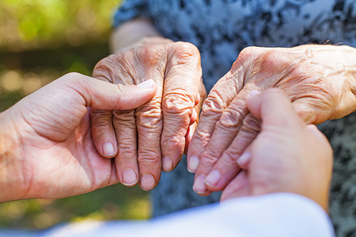 elderly_woman_holding_hands_with_nurse